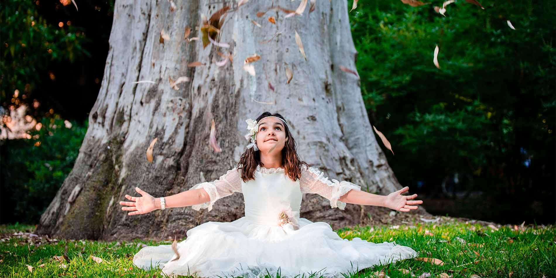 niña de comunión sentada en el suelo tirando hojas secas al vuelo en su fotografía de comunión en Sevilla