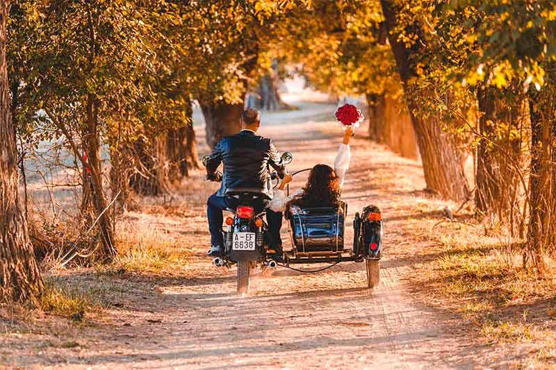 Portada del vídeo de boda de Lourdes y Tareck de espaldas alejándose en un sidecar en un camino entre árboles