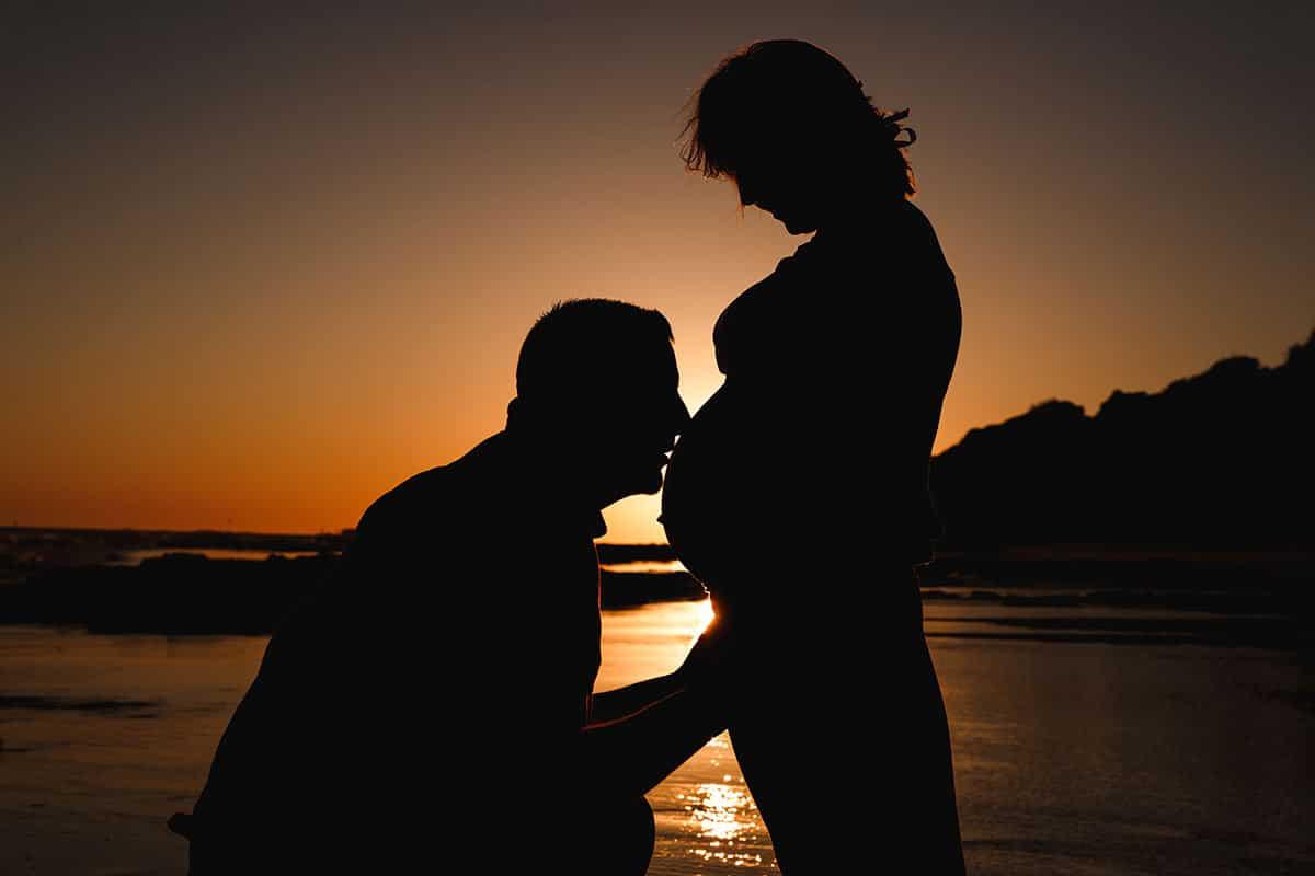 Sesión de fotos de embarazo, mujer embarazada en la playa a contraluz al atardecer silueta del marido besando la barriga