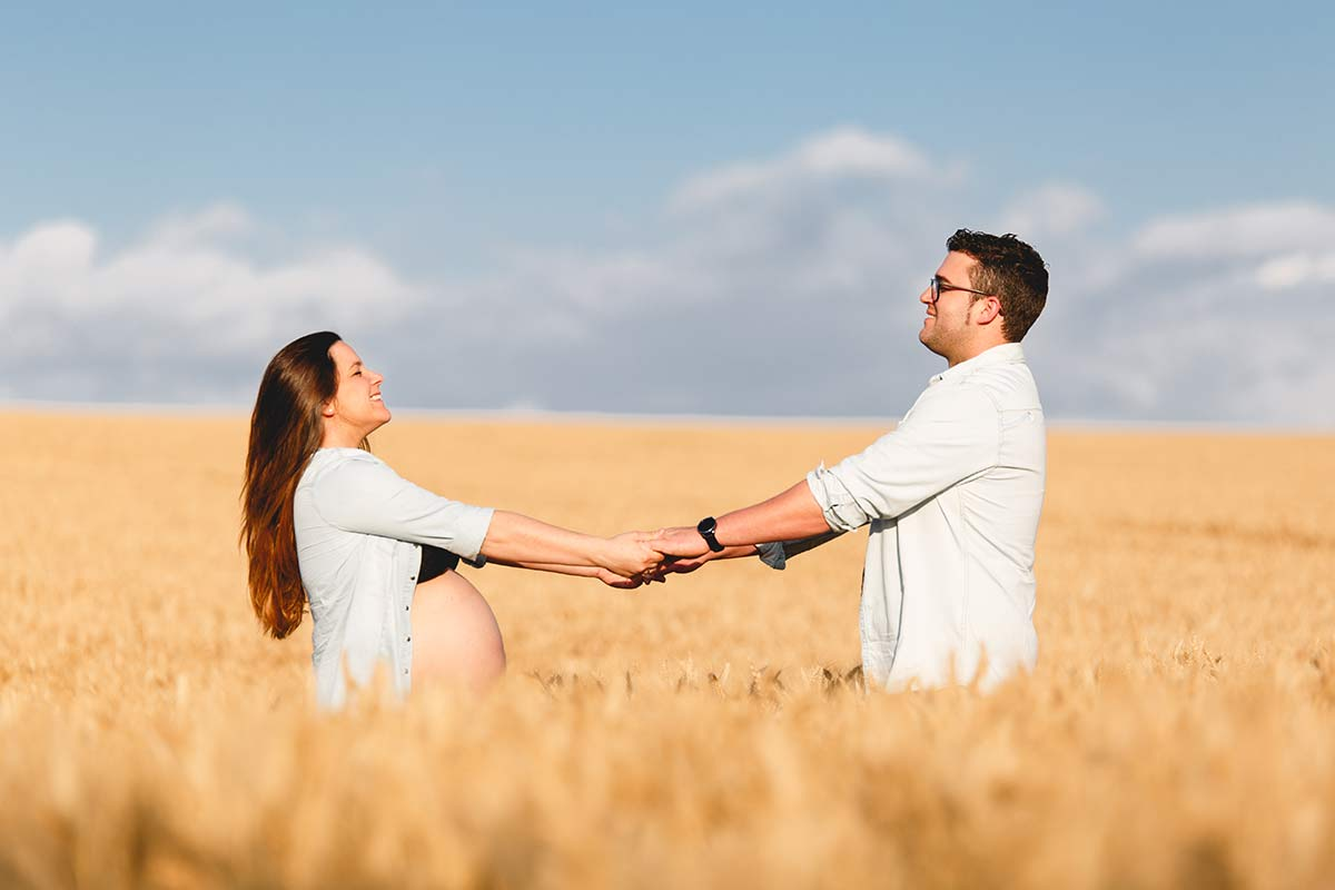 fotografía de embarazo en el campo, mujer embarazada y su marido cogidos de las manos dentro de un sembrado de trigo