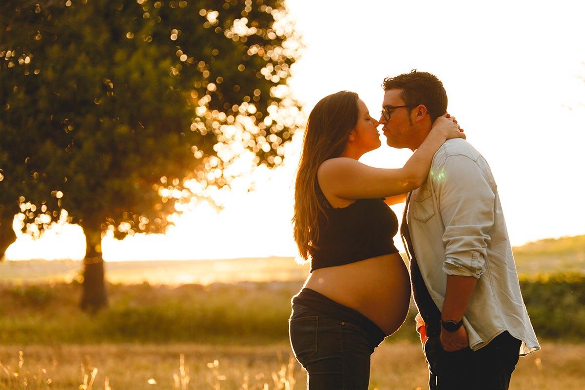 sesión de fotos de mujer embarazada y su pareja besándose en la puesta de sol