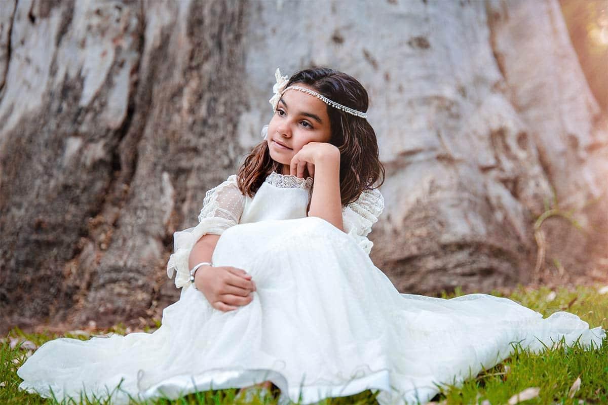Arantxa vestida de comunión sentada en el suelo junto al tronco de un gran árbol