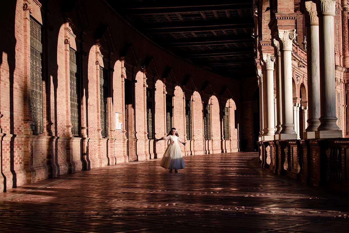 Arantxa vestida de comunión bailando entre columnas, en el pasillo de la plaza de España