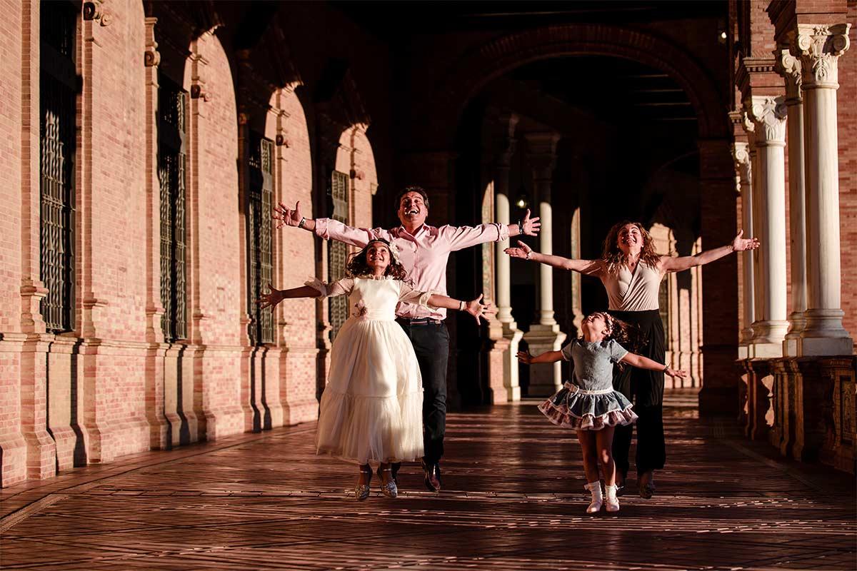 fotografía divertida de Arantxa saltando en el pasillo de plaza de España, entre columnas, junto a su hermana y sus padres, en su reportaje de comunión