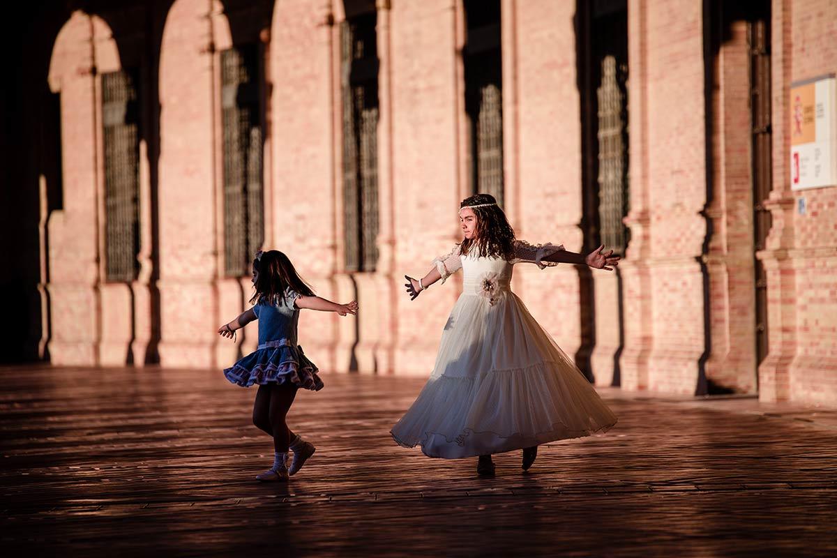 fotografía original y divertida de niña de comunión con su hermana dando vueltas con los brazos extendidos, en elpasillo de la plaza de España