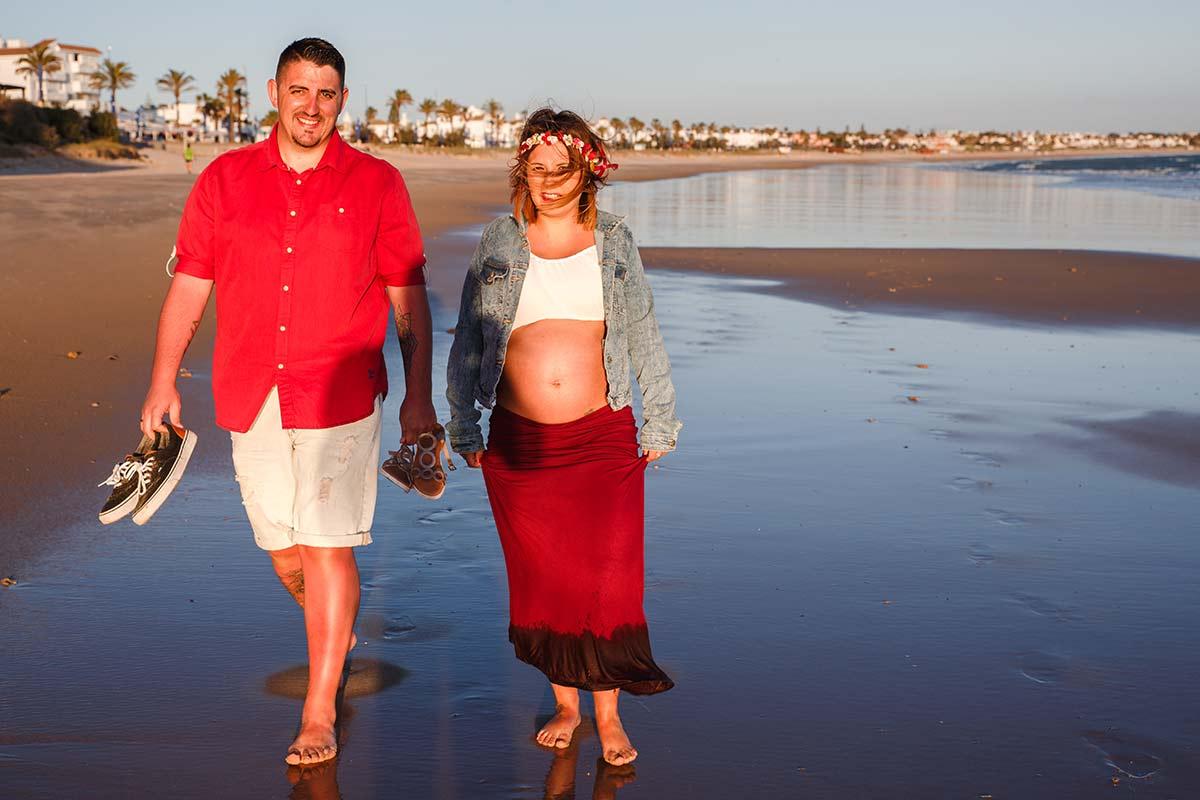foto espontánea y natural de embarazada con su pareja paseando por la playa con los pies descalzos sobre la arena mojada